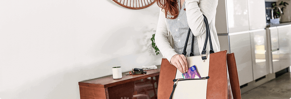 Woman placing Kleenex tissues in purse.